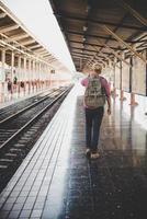 ung hipster man går genom tågstationen foto