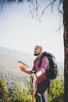 vandrare med karta och stor ryggsäck som reser till berget foto