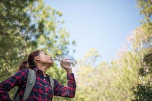 glad kvinna turist med ryggsäck dricksvatten i naturen foto