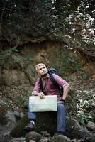 ung trött vandrare med ryggsäck sitter i skogen foto