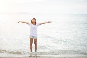 ung vacker kvinna sträcker armarna i luften på stranden med bara fötter foto