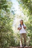 aktiv ung kvinna vandrare går genom skogen foto