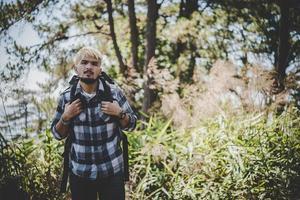 ung man reser med en ryggsäck i naturen foto