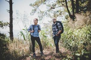 par som vandrar genom skogen till bergstoppen
