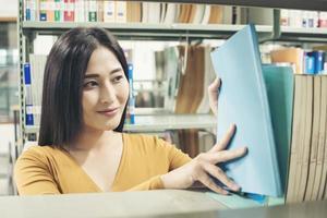 ung asiatisk student vid biblioteket som läser en bok