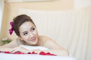 vacker le kvinna med blommor som vilar i spaet före massage foto