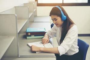 ung asiatisk student läser i biblioteket foto