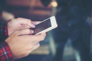 närbild av kvinnan som håller en mobiltelefon med reflektion från fönstret foto