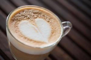 närbild av cappuccino kopp med hjärtformade mjölk mönster på café foto