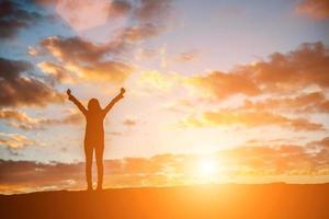 glad ung silhuett av en kvinna som hoppar mot den vackra solnedgången foto