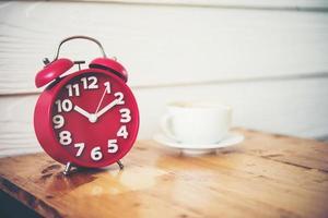 röd väckarklocka med kaffe på träbord foto