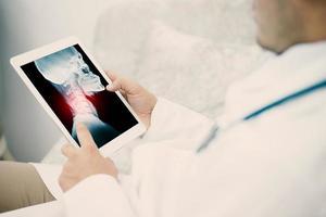 medicinsk ung manlig läkare som utforskar lungroentgenogram på tablett i klinik foto