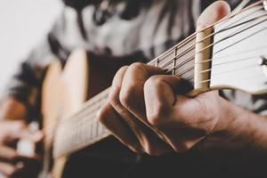 närbild av manhand som spelar gitarr foto