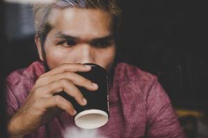 hipster man som håller en kopp kaffe foto