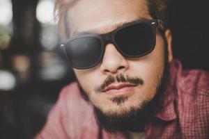 ung hipsterman som bär solglasögon som sitter vid ett barbord på ett kafé