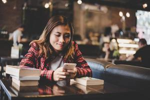 hipster tonåring sitter och njuter av en bok på ett kafé foto