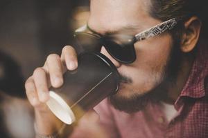 ung man sitter på ett kafé och dricker en kaffe foto