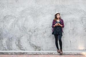 porträtt av en ung hipsterkvinna som lyssnar på musik med smartphonen foto