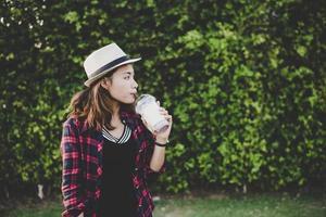 vacker hipster kvinna dricka en milkshake utomhus foto