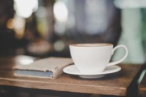 kopp kaffe med en bok i ett kafé foto