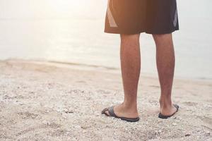 ung mans ben i sandaler på stranden