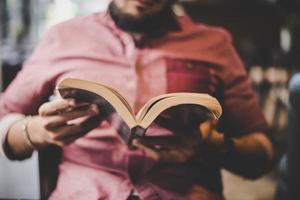 hipster skäggig man läser bok i café.