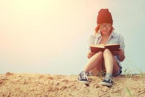 vacker ung kvinna som läser en bok på stranden