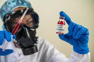 forskare som bär skyddsmasker och handskar som håller en spruta med ett vaccin för att förhindra covid-19