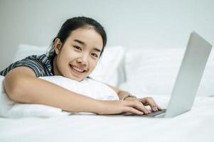 en kvinna som bär en randig skjorta som leker på sin bärbara dator på sin säng foto