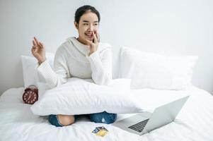 ung kvinna som sitter på hennes säng som lyckligt ler foto