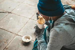 en hemlös man sitter insvept i tyg och äter nudlar foto