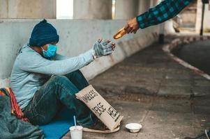 brödmakaren ger till en tiggare vid sidan av vägen foto