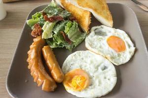 stekt ägg, korv, sallad och rostat bröd på tallrik och träbord
