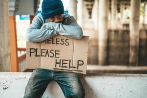tiggaren sitter på en vägbarriär med hemlösa snälla hjälp skylt foto