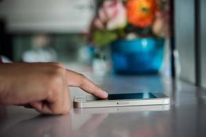 närbild av en kvinnas hand med en mobiltelefon foto