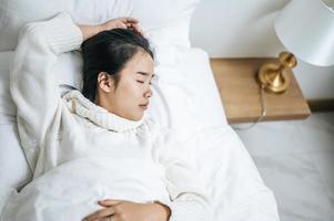 ung kvinna som bär vit skjorta som bara vaknar upp i sängen foto