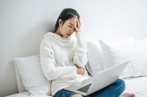 en kvinna som sitter i sängen och leker på sin bärbara dator och känner stress foto