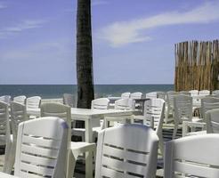 utomhusbord och stolar vid havet foto