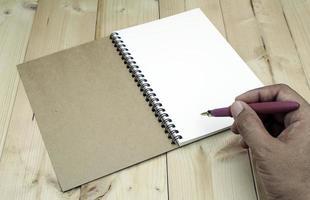 person som skriver i anteckningsboken foto
