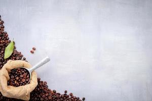 mörka rostade kaffebönor i påsar med hampasäck foto