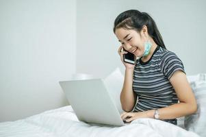 kvinna som leker på sin bärbara dator och pratar i telefon foto