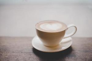 vintage latte art kaffe med hjärtform på träbord foto