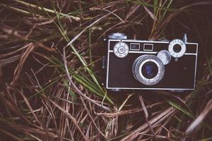 gammal vintagekamera i ett gräsfält foto