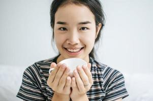 ung kvinna som håller en kaffekopp i sängen foto