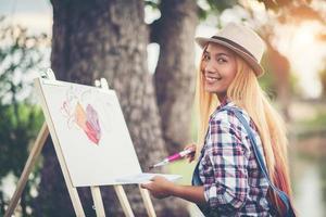 vacker flicka ritar en bild i parken foto