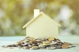 hög med mynt med ett litet modellhus foto