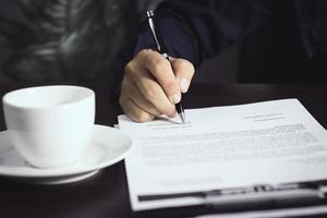 person som skriver i ett kontrakt foto