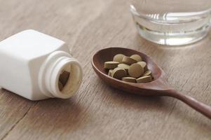 örtmedicin i piller på träbord foto