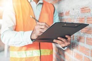 ingenjör eller inspektör som kontrollerar pågående arbete på byggarbetsplatsen foto