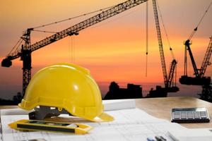 skyddshjälm med konstruktionsobjekt på bord med stadsbild foto